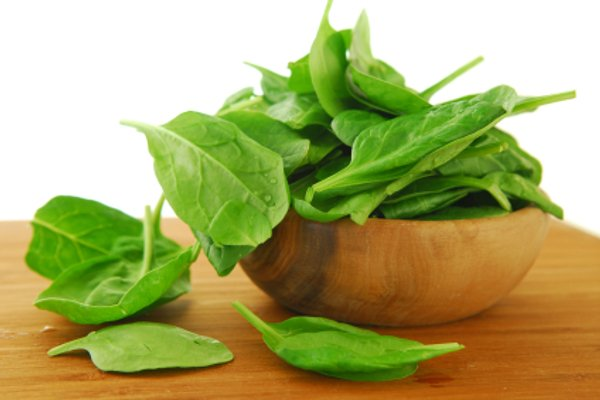 Fresh spinach iin a wooden bowl on a cutting board